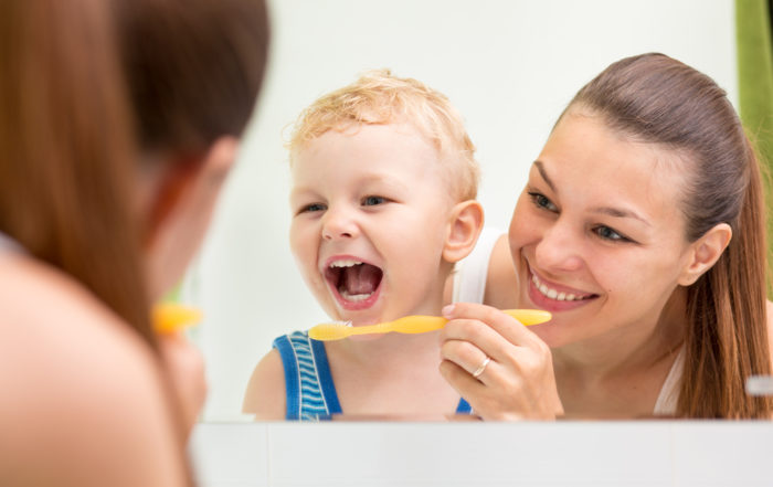 Mother teaching infant to brush
